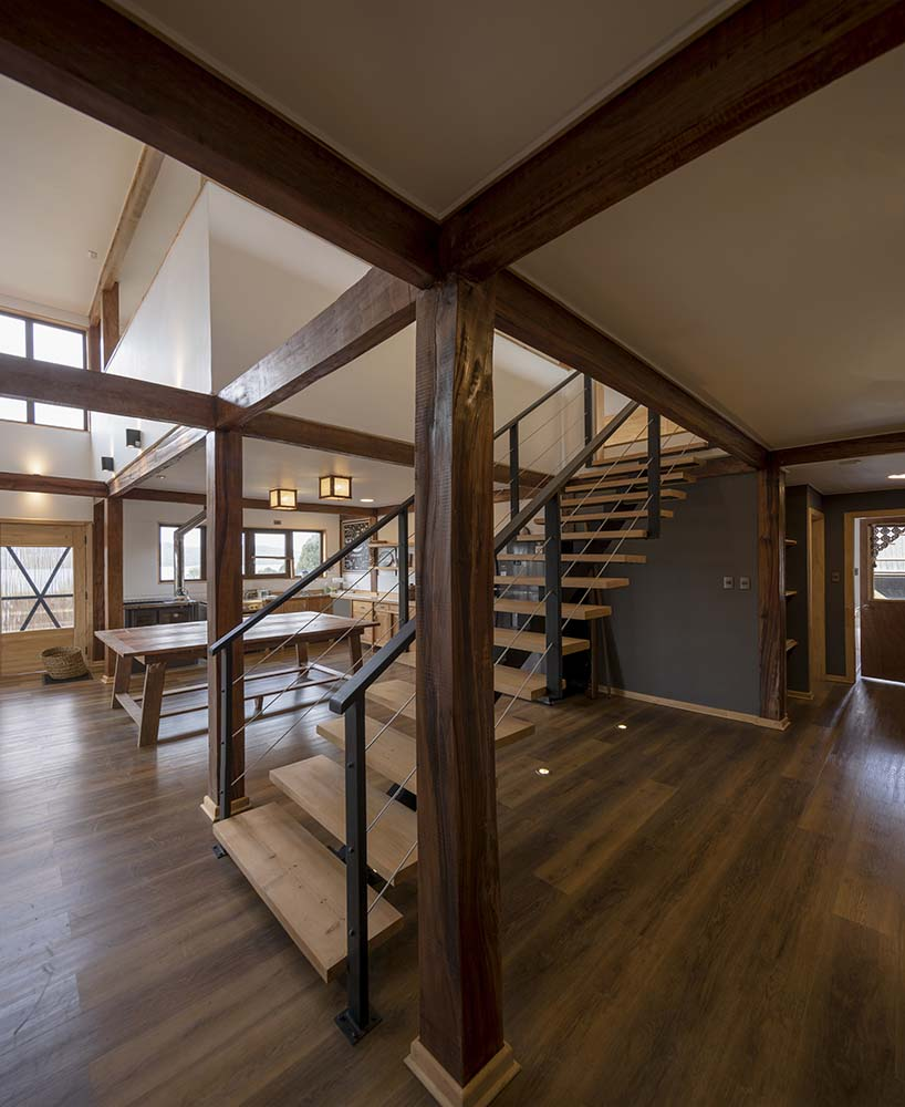 This view of the great room showcases more of the thick wooden support beams that extend to the exposed beams of the ceiling.