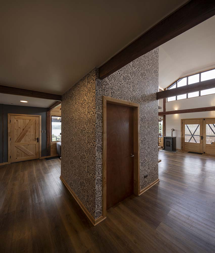 On the side of the large pillar is a wooden door that makes it stand out against the patterned wallpaper.