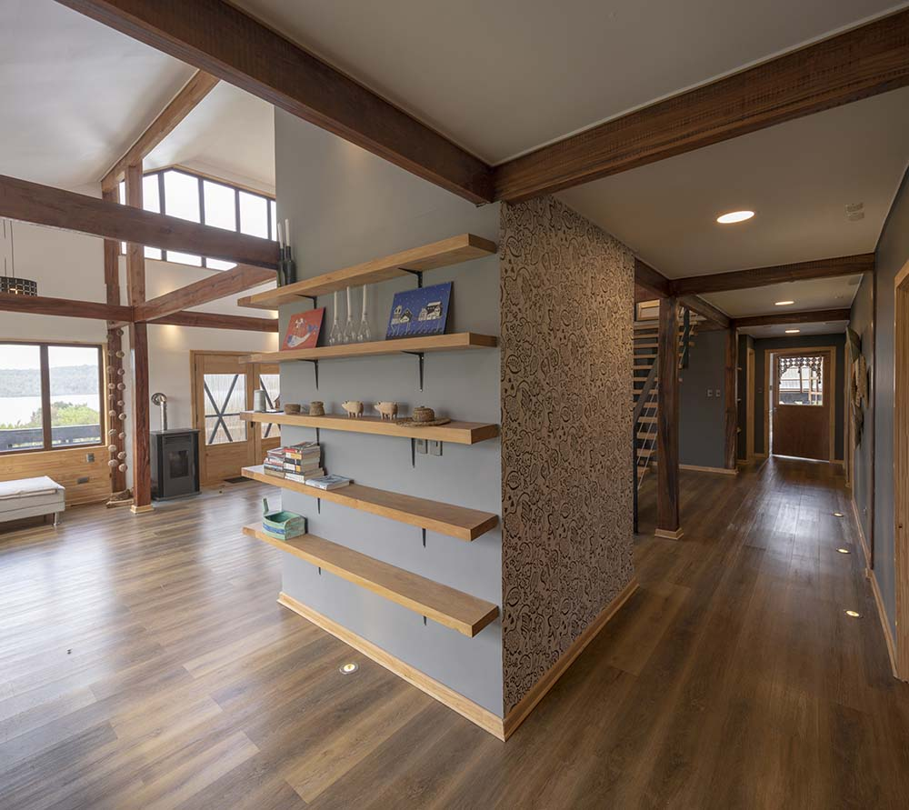 The two sides of the pillar facing the living room and kitchen have floating wooden shelves.