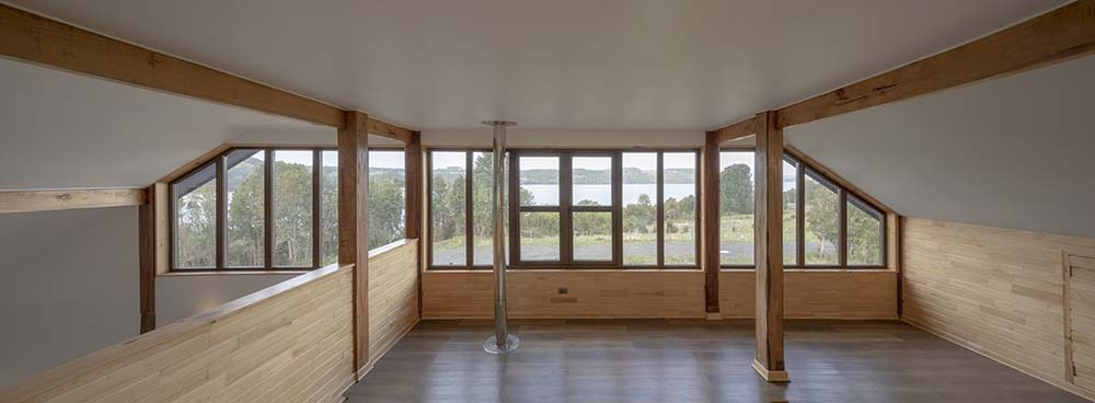 This is a view of the house upper level with a low ceiling, natural lighting from glass walls.