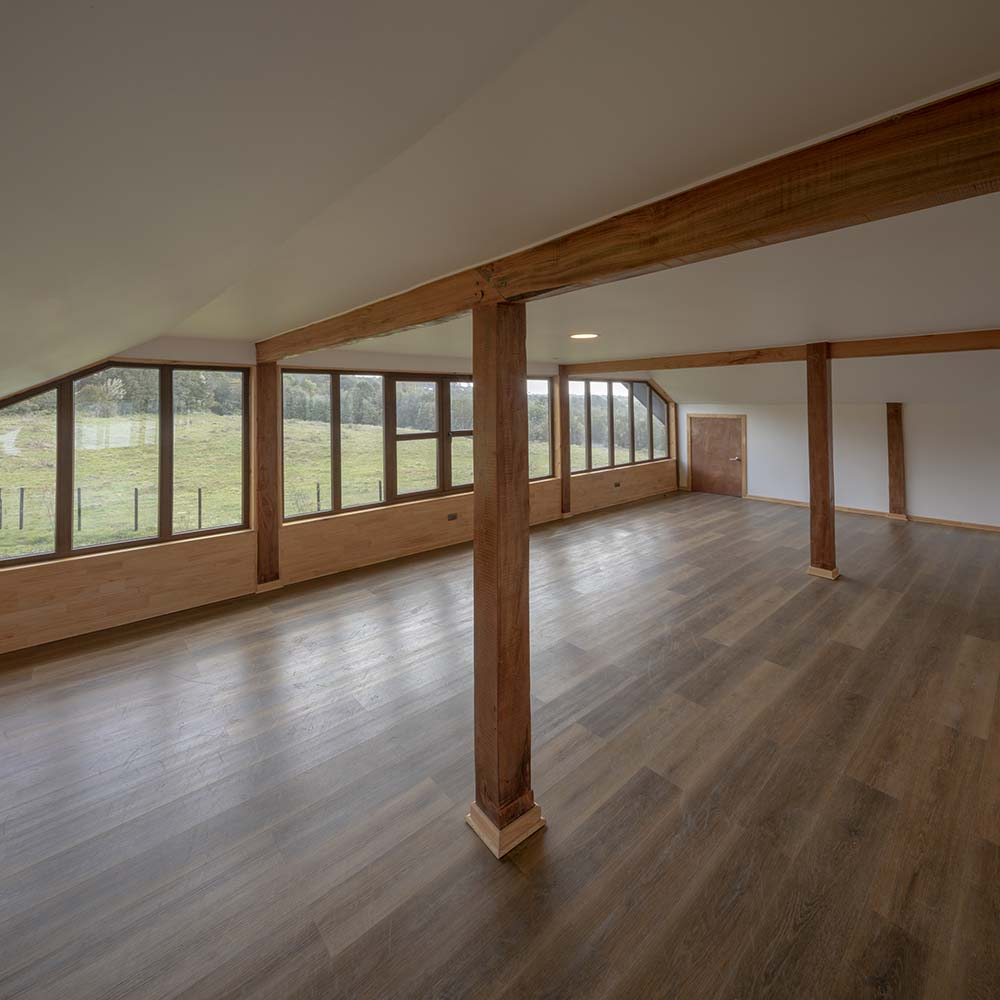 This is another large room on the upper floor of the house with a wide hardwood flooring and a ceiling that has exposed beams that match the window frames.