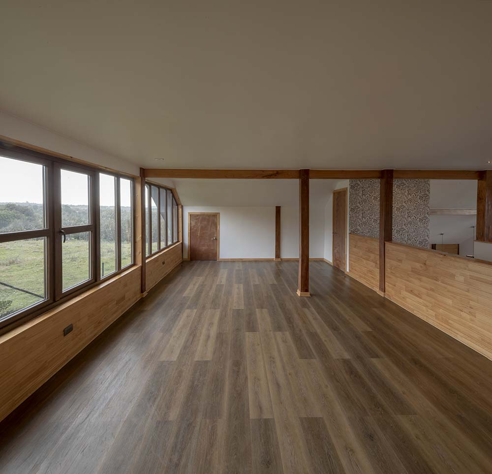 This is another view of the spacious and bright room with a dark hardwood flooring that contrast the arched ceiling.