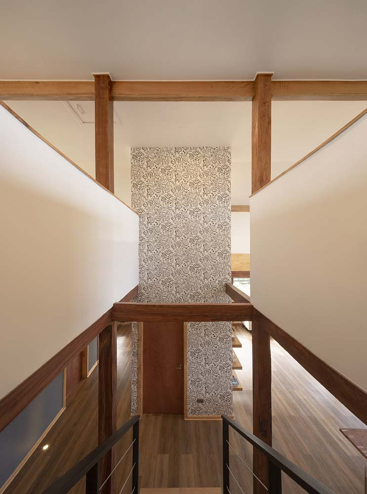 This is a look down the staircase from the second level landing with a view of the large pillar with a door.