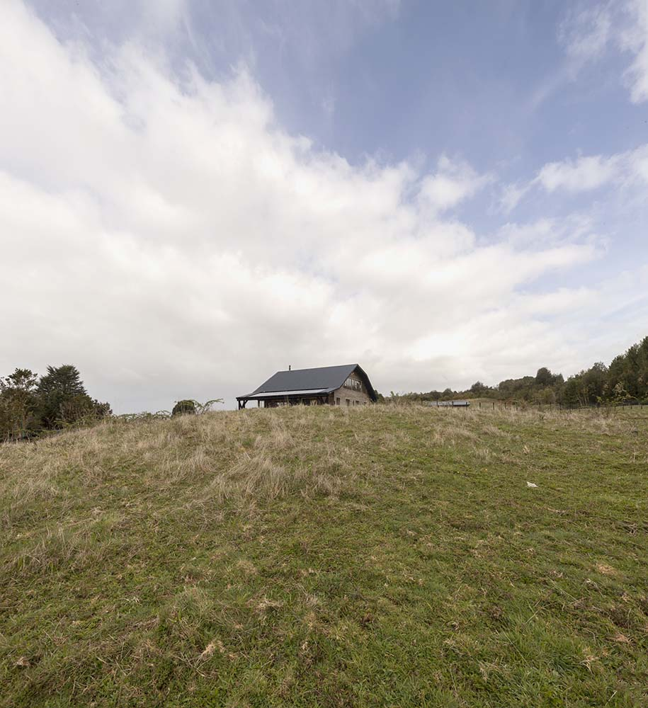 This s a far off view of the house featuring the tall hill with grass lawns.