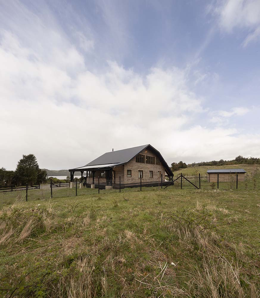 The house is surrounded by outer fences with wire and dark wood to match the tone of the roof.