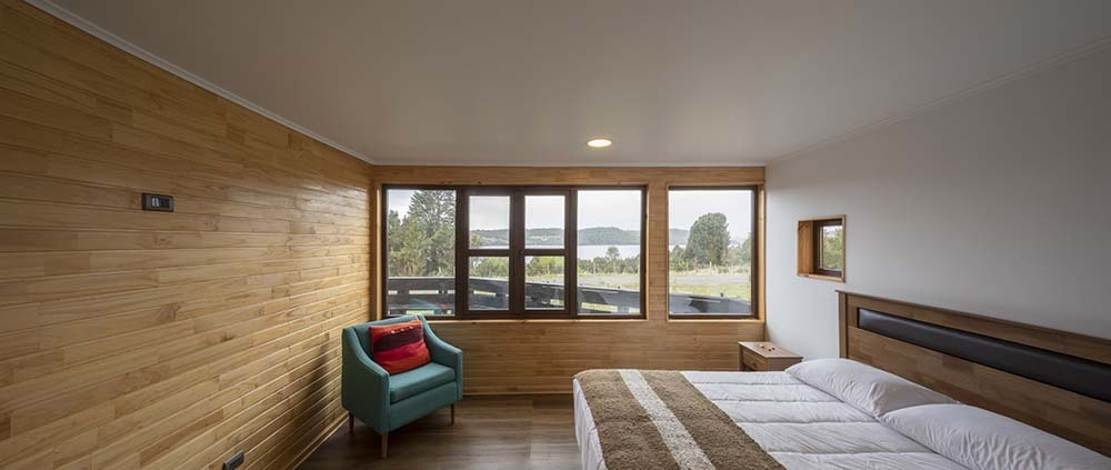 This is a close look at the bedroom that has a bed and a cushioned arm chair on the far corner of the room by the row of windows.