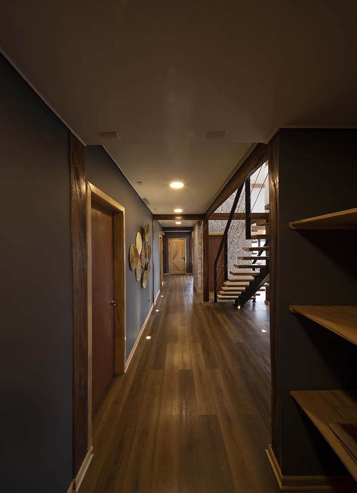 This is another view of the hallway with a view of the staircase, the large pillar and has a built-in set of shelves on the side.