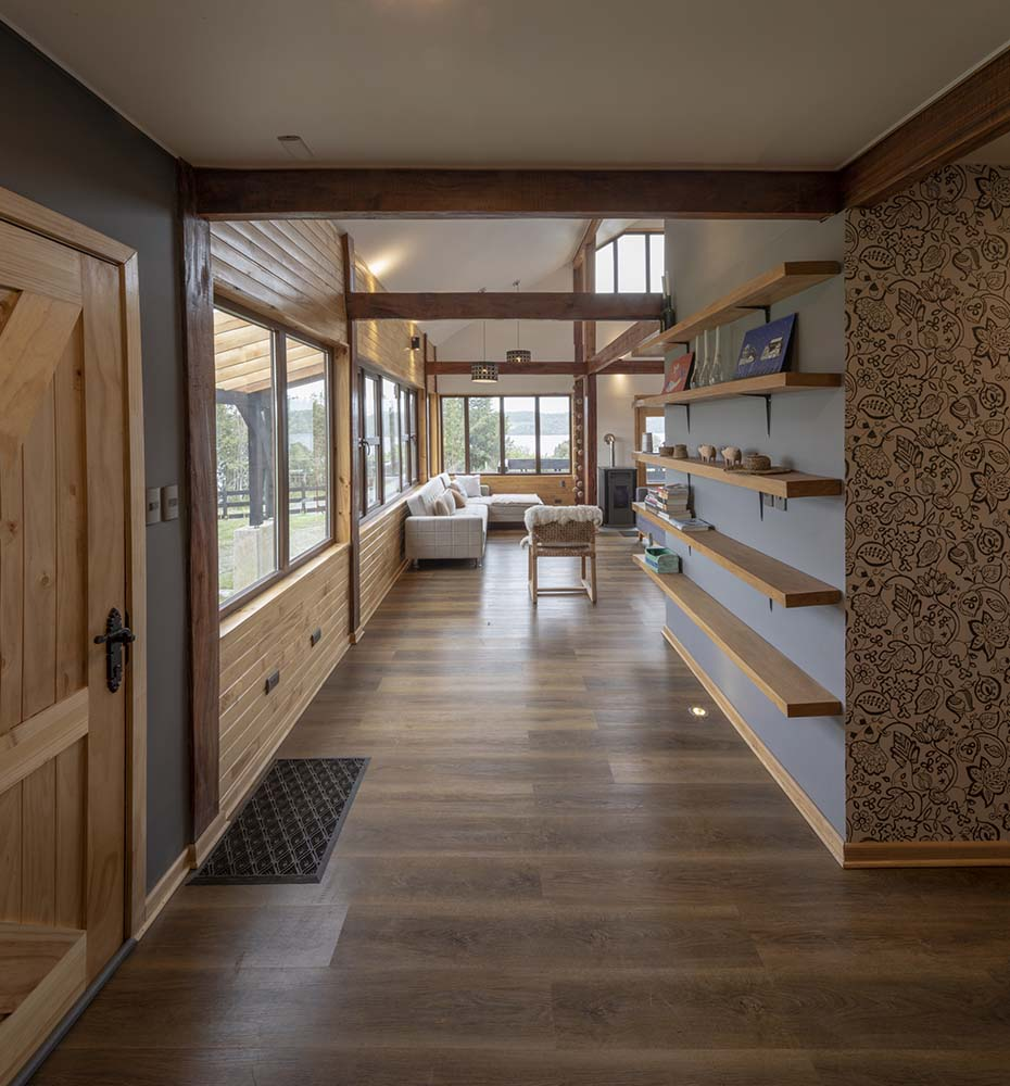 Upon entry of the house, you are welcomed by this simple foyer with a wooden door and a large pillar with floating wooden shelves.