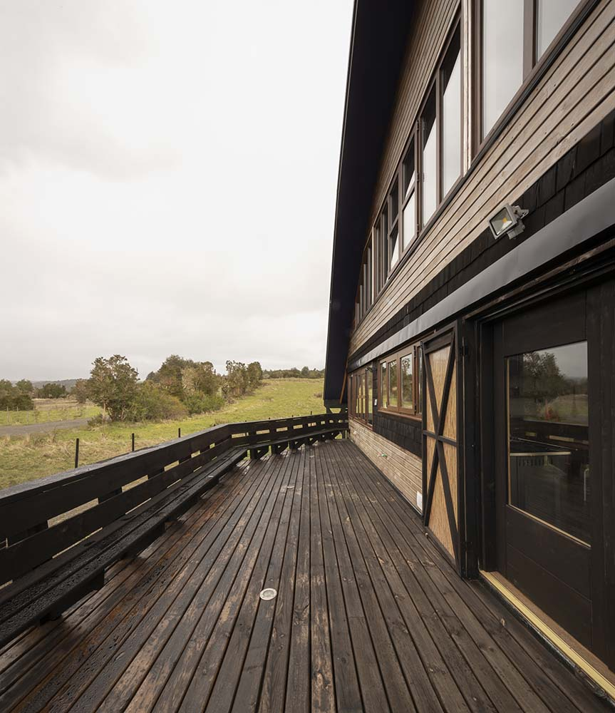 This is a view of the house's terrace and porch with dark wooden railings on the sides.