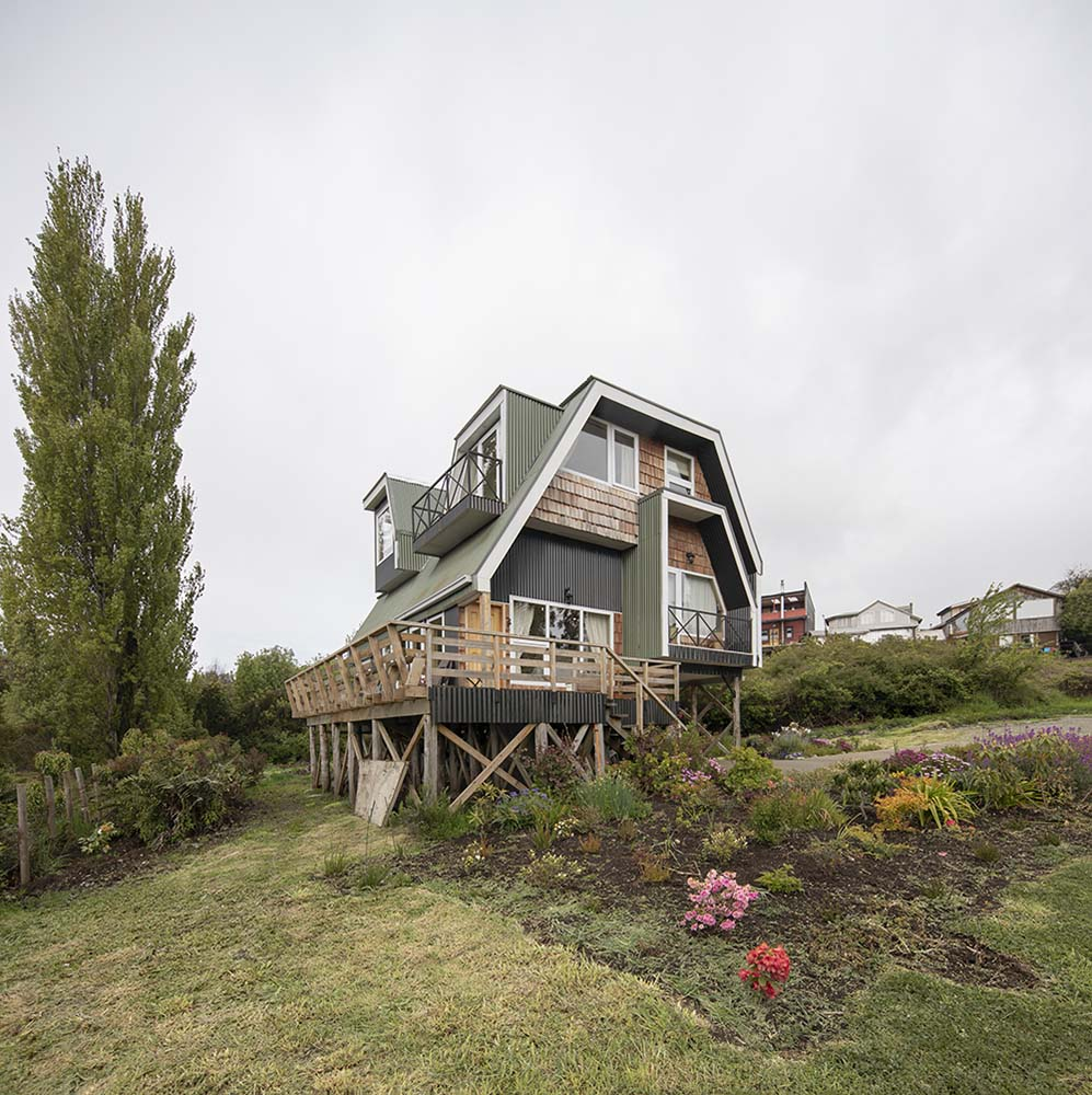 This is a side elevation of the house showcasing the large balcony terrace on the side with wooden railings.