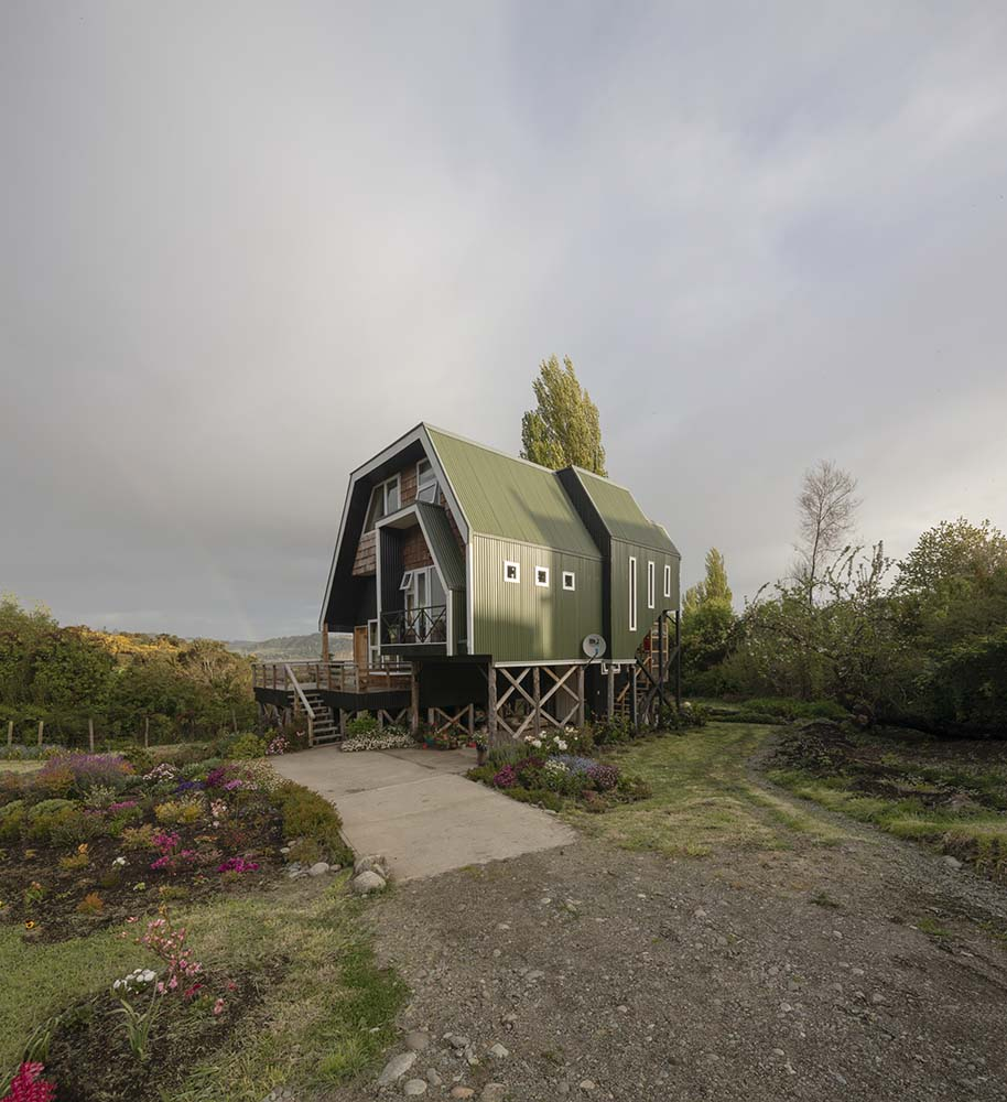This is a view of the front of the house that shows the wooden support beams at the bottom of the house as well as the surrounding landscape filled with flowers.