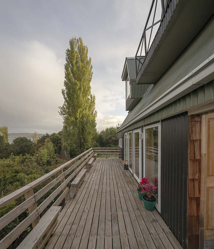 This is the large lower balcony terrace of the house with a wooden shiplap flooring to match the wooden railings.