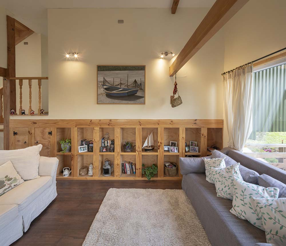 The living room has a couple of sofas with a background of wooden shelves, wall-mounted artwork and wooden ceiling beams.