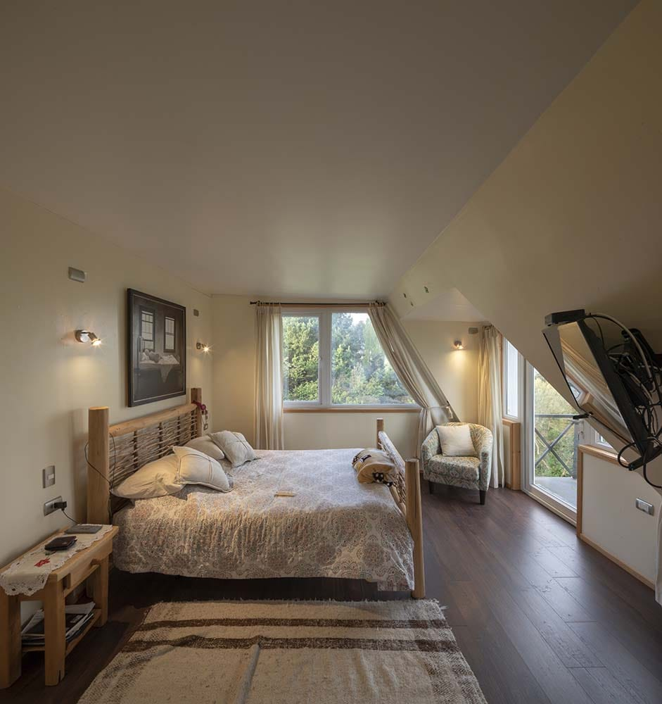 This other bedroom has a large wooden sleigh bed contrasted by the dark hardwood flooring and complemented by the surrounding beige walls and ceiling.