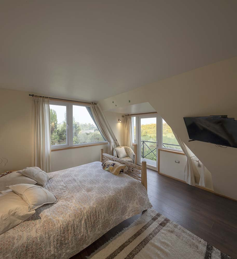 Across from the bed is a large window and a set of glass doors that lead to a balcony.