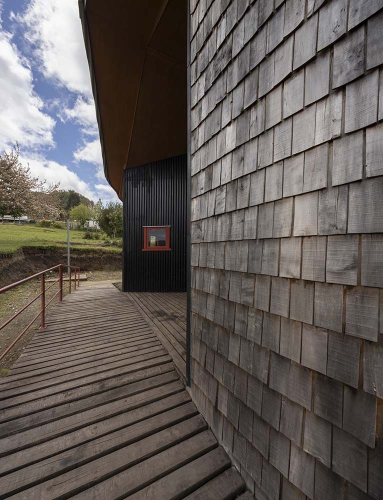 This is a closer look at the wooden shingles of the exterior wall that matches well with the wooden deck walkway.