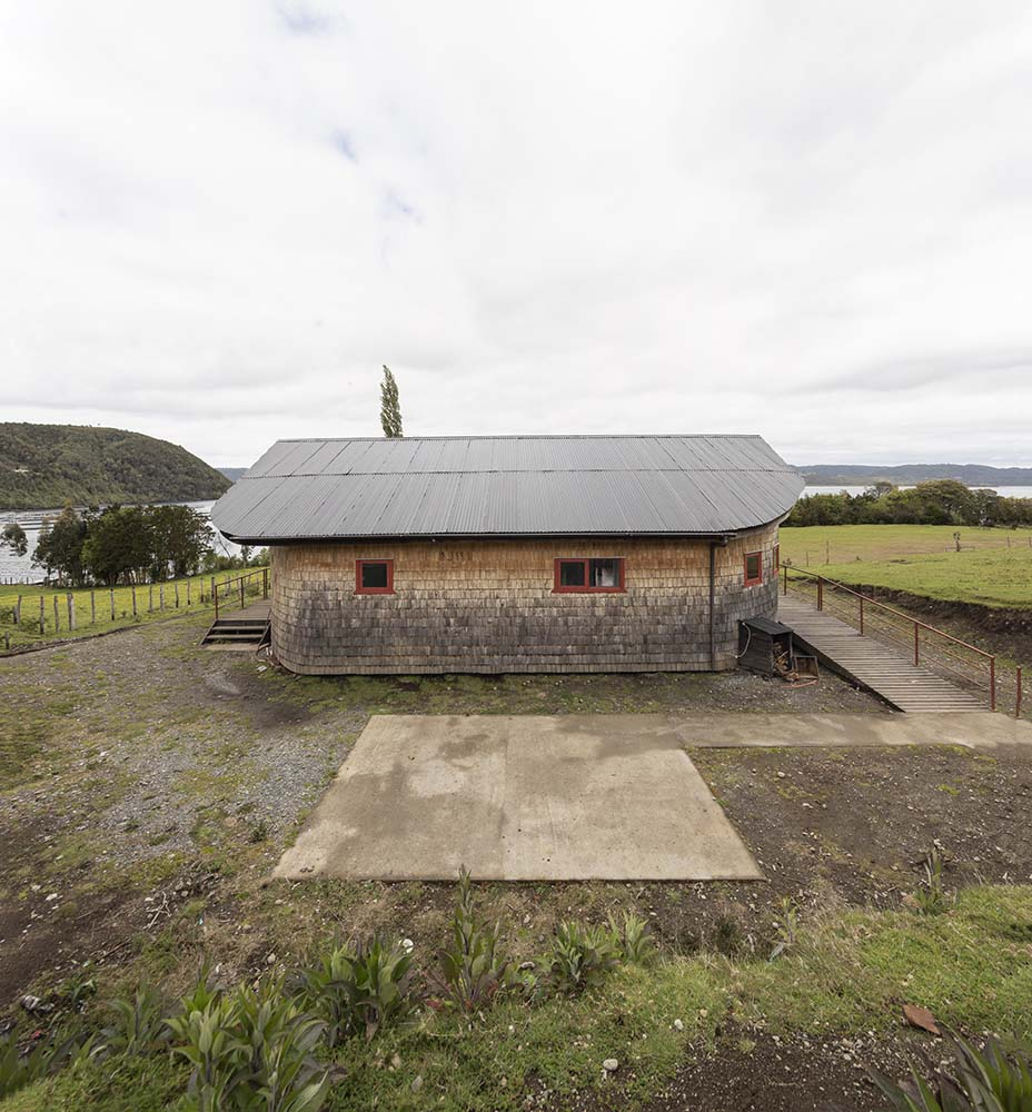 This is an aerial view of the house showcasing the side with a space for an outdoor dining area and the arched roof of the house.