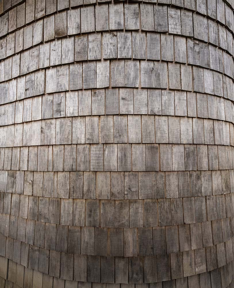 The wooden shingles of the exterior walls have a rustic aesthetic to it.
