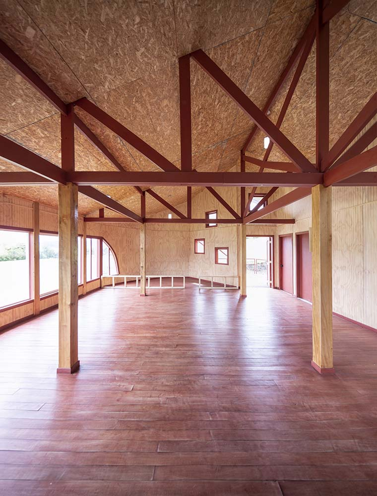 This is a view of the open floor area of the interior with wooden pillars and exposed beams.