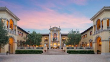 This is a close look at the front of the massive mansion that has warm exteriors complemented by the lush landscaping and the warm glow of the multiple windows. Images courtesy of Toptenrealestatedeals.com.