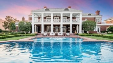 This is a look at the back of the house showcasing a large pool, lush landscaping and a house that has a large balcony supported by large pillars. Image courtesy of Toptenrealestatedeals.com.