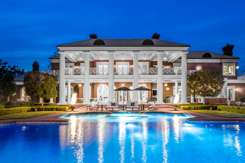 This is a nighttime view of the back of the house that showcases the glow of the large pool that matches with the glow of the house coming from its windows and exterior lights. Image courtesy of Toptenrealestatedeals.com.