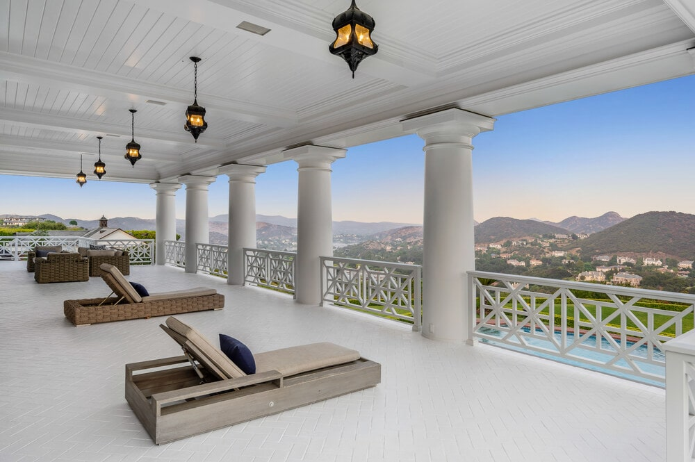 This is a close look at the large balcony at the back of the house with massive pillars, pendant lights and a number of lounge chairs facing the view. Image courtesy of Toptenrealestatedeals.com.