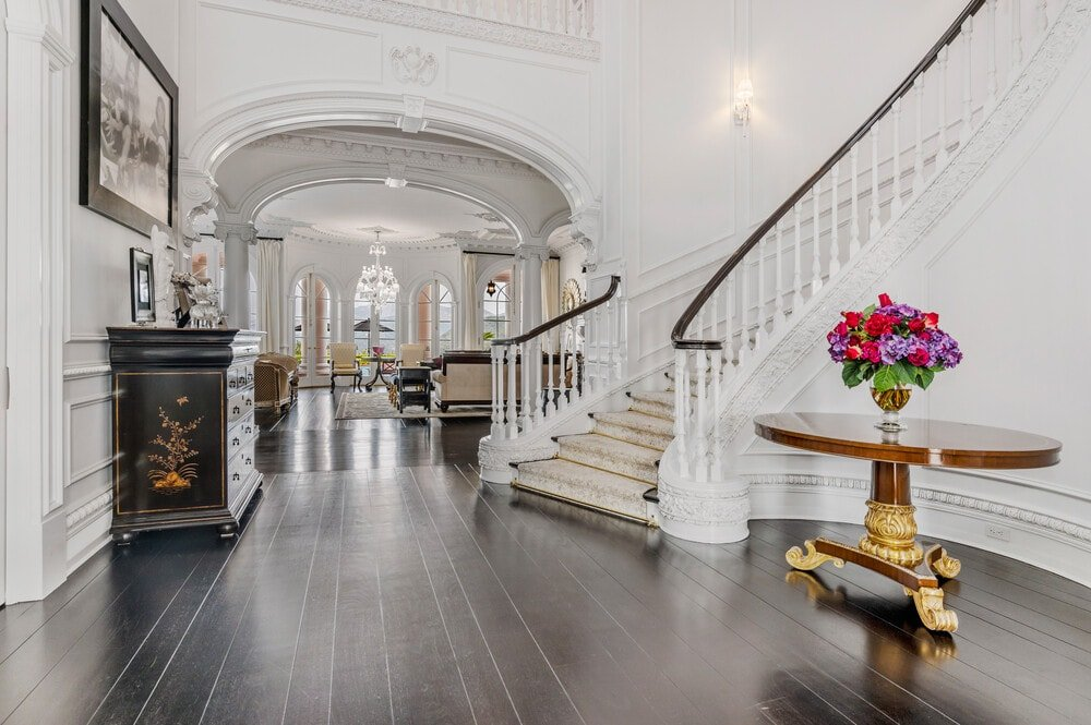 Upon entry of the house, you are welcomed by this grand foyer that has a curved staircase, dark hardwood flooring and contrasting bright white walls. Image courtesy of Toptenrealestatedeals.com.