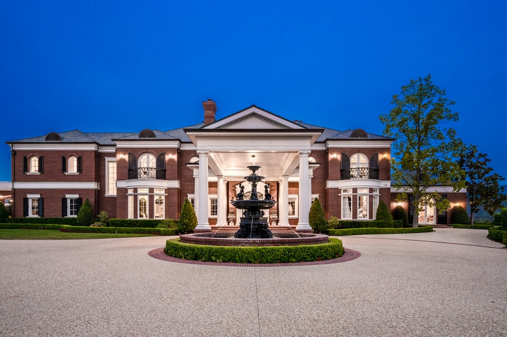 This is the front of the house that has a wide courtyard and driveway dominated by a large fountain in the middle and a view of the dark exteriors of the house. Image courtesy of Toptenrealestatedeals.com.