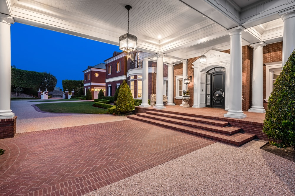 This is a close look at the main entrance of the house with a large white tray ceiling, bricked walkway, bricked steps and a number of white pillars. Image courtesy of Toptenrealestatedeals.com.