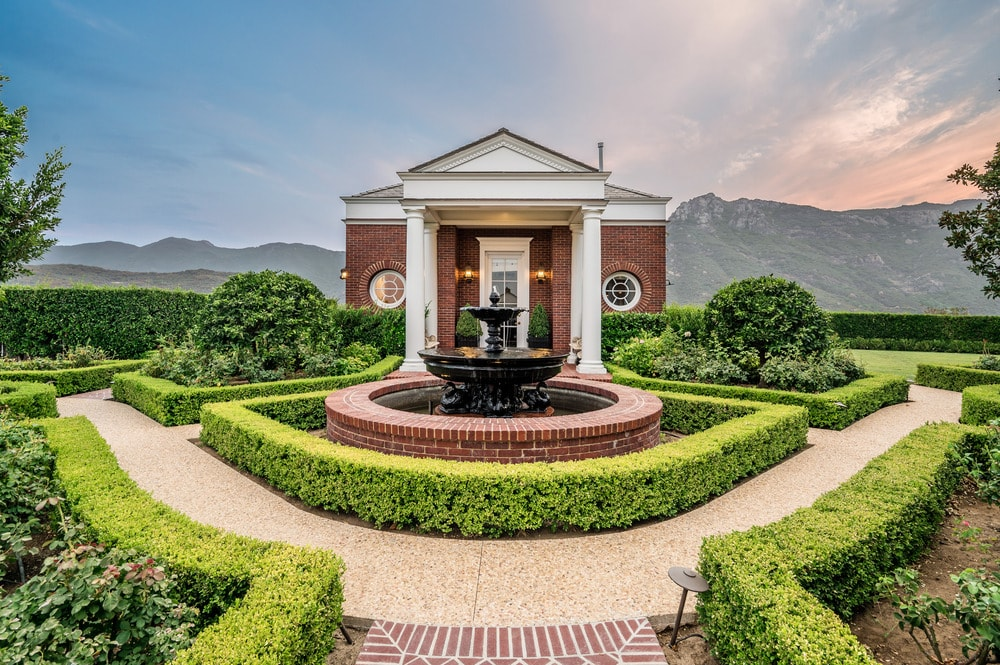 This is a close look at the garden of the house with lush landscaping of shrub hedges that are properly maintained surrounding a large fountain in the middle. Image courtesy of Toptenrealestatedeals.com.
