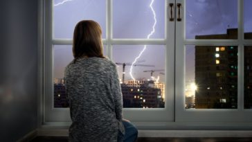 A girl watching the storm through a set of French glass windows.