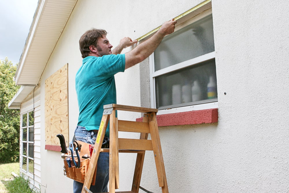 A man measuring the windows for storm window installation.
