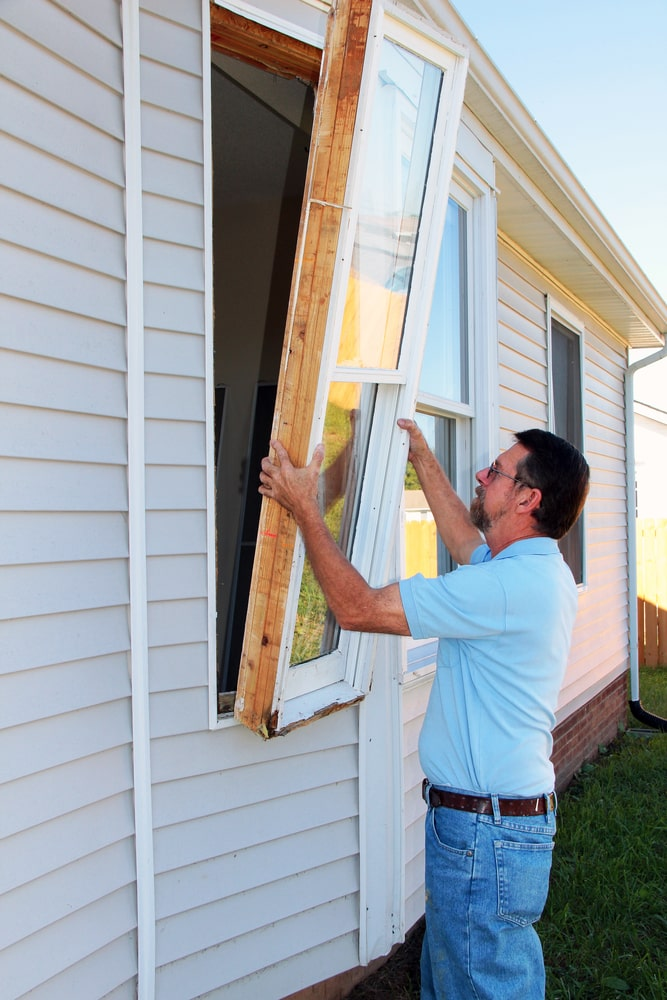 A man installing a storm window.