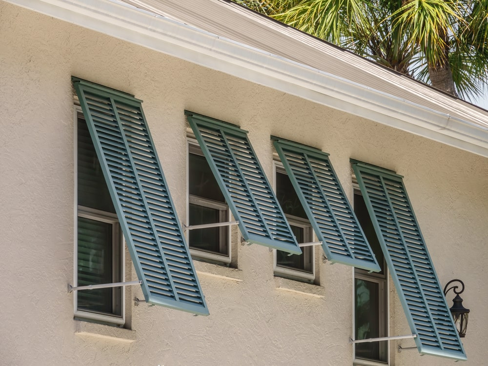 A close look at a house with storm shutters on its windows.