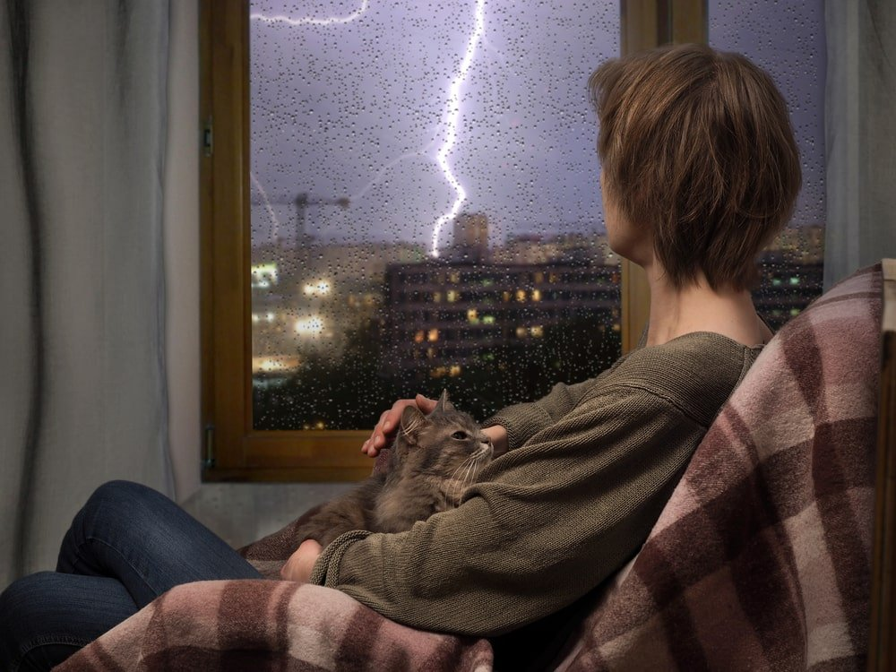A woman watching the storm outside through a set of glass doors.