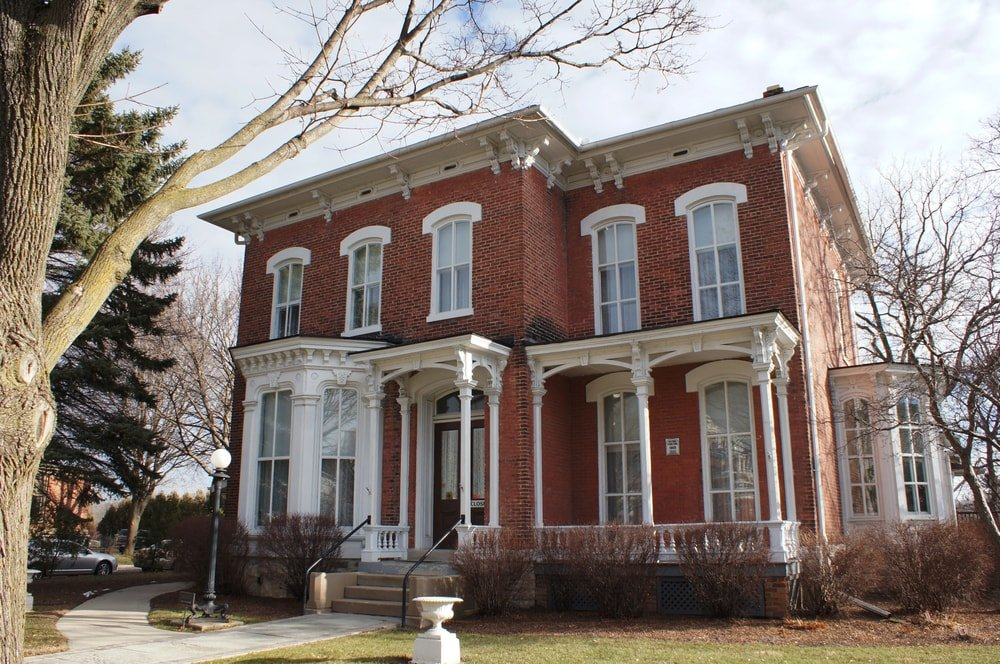 This is an Italianate-style brick home with double hung windows and eve brackets.