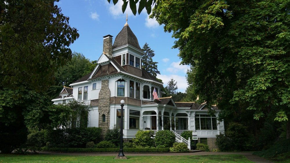This is a look at the front of an Italianate-style home with a central cupola and surrounded by lush landscaping.