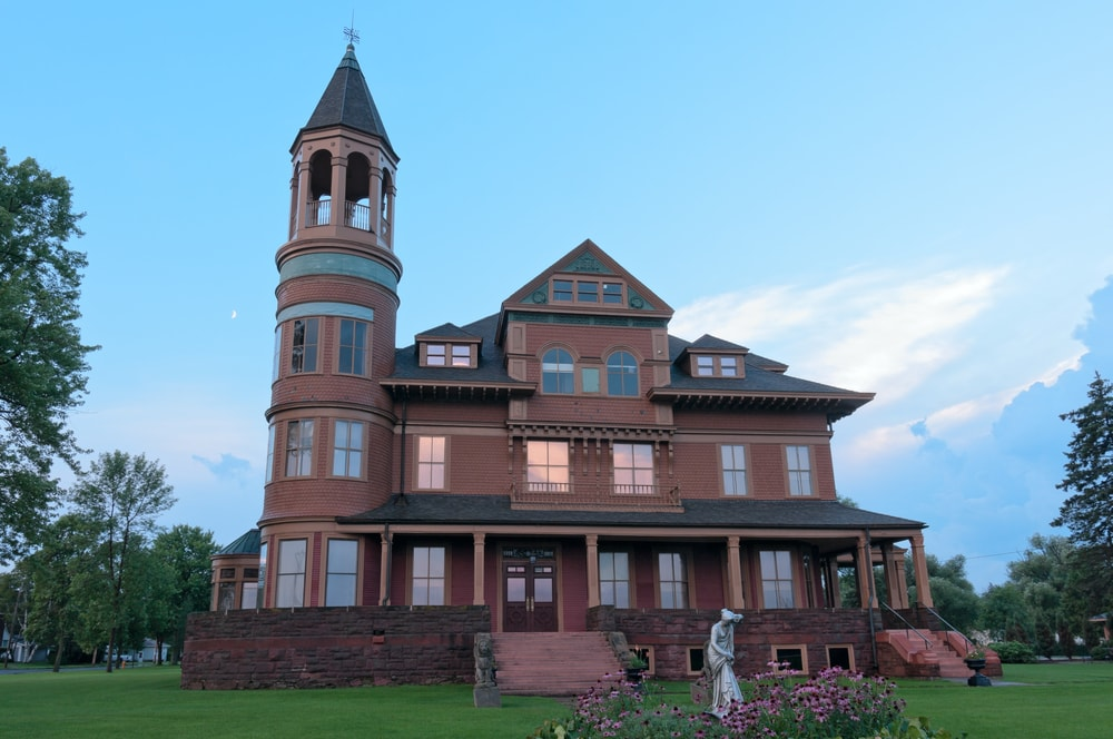 This is a Queen Anne style Victorian home with a tall tower on one side and a dark brown tone to its exterior walls.