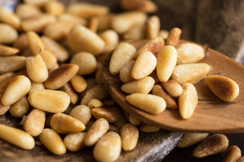 A close look at some roasted pine nuts with a wooden spoon.