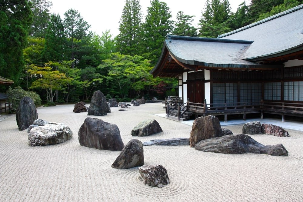 This is a close look at the zen garden of a Japanese temple with large decorative rocks and sand adorned by the patterns.