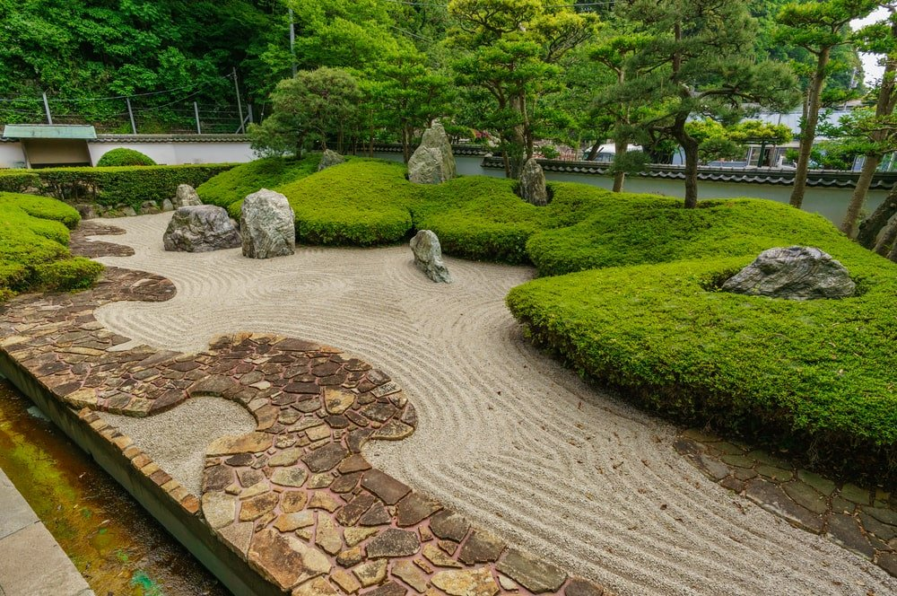 This is a zen garden with decorative rocks, patterned sand and shrubs topped with trees.