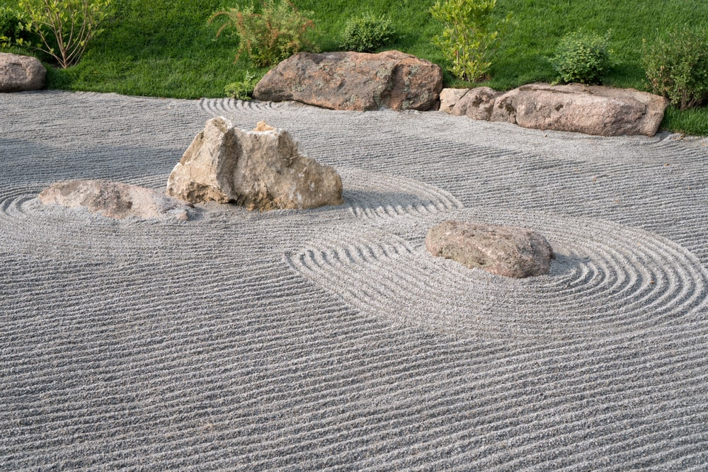 This is a close look at the patterned sand and decorative rocks of a zen garden.