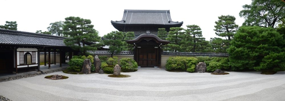A serene zen garden of rocks, shrubs and trees that complement the Japanese temple.