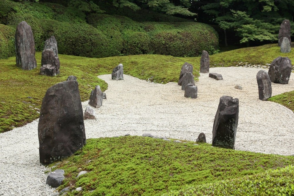 This zen garden has decorative rocks, sand with patterns and a surrounding grass lawn for a color contrast.