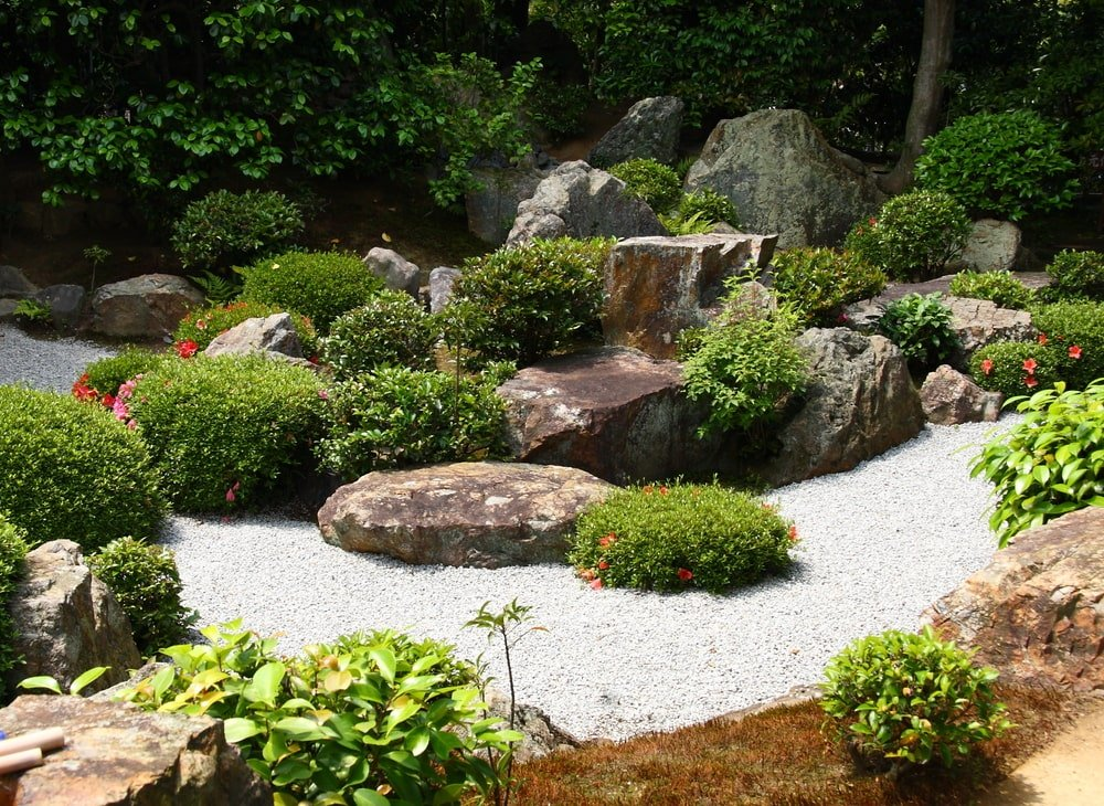 This zen garden has a alrge decorative rock formation adorned with gravel and various flowering shrubs.