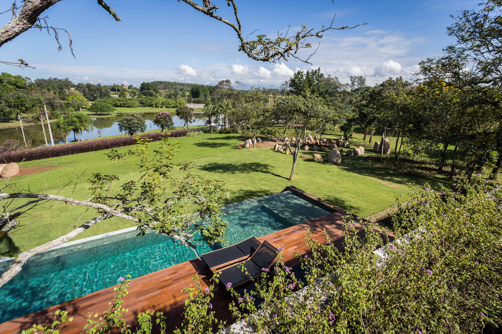 The pool is complemented by the large grass lawn surrounded by tall trees and a water scenery on the far distance.