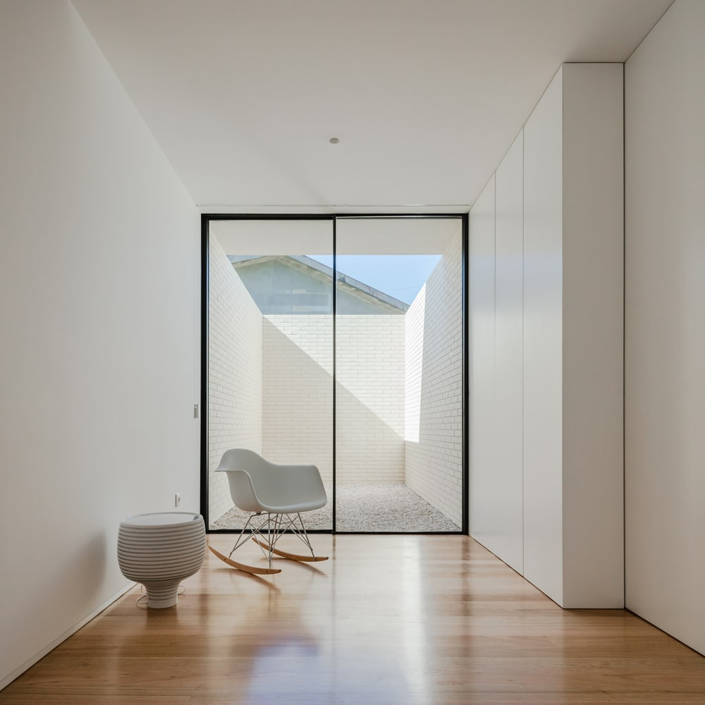 This is a corner of the house that has hardwood flooring and white walls brightened by the glass doors on the far side.