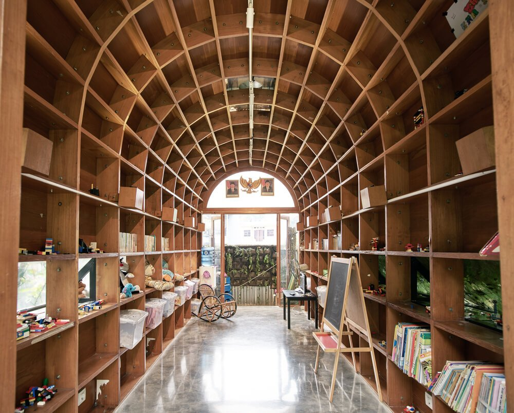 The arts and crafts room has built-in wooden shelves that extend to the eceiling.