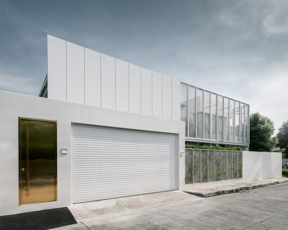 On the side of the golden main door is the large garage with a garage door that pairs well with the exteriors.